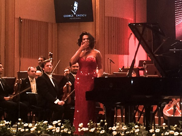 Khatia Buniatishvilli sending kissses to the audience. Behind Israel Philharmonic Orchestra.
